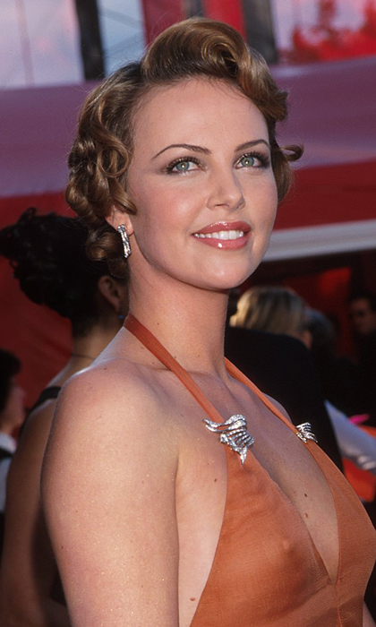 Charlize is resplendent in an orange Vera Wang gown and Marilyn Monroe-inspired curls on the red carpet at the 2000 Oscars. Photo: © Getty Images