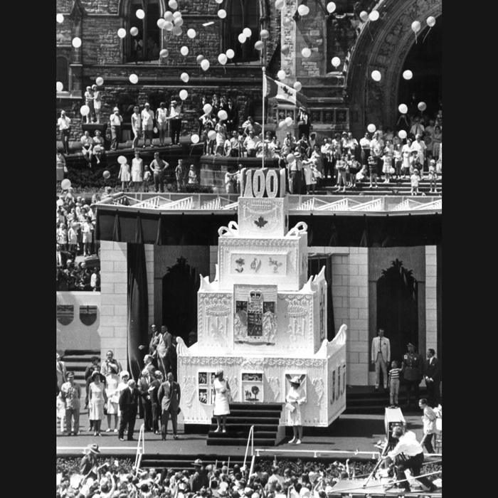 "CANADIAN CENTENNIAL, 1967: Happy 100th birthday, Canada! The Queen visited Ottawa to mark a very special Canada Day – 100 years on from the first Dominion Day in 1867. With an impressive 10-metre ""birthday cake"" (it was actually made of plywood) rising behind her, Her Majesty celebrated alongside her Canadian subjects as she took part in the extensive festivities on Parliament Hill.