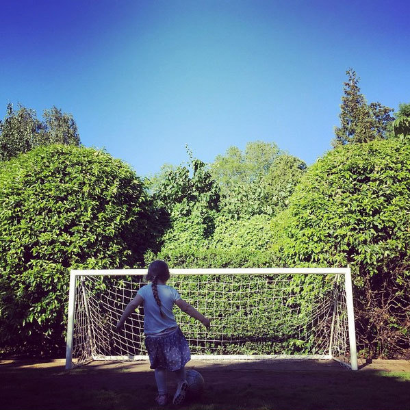 "Practising her football skills. David explained: ""Harper Seven taking lessons from her brothers ( oh and her dad )""
