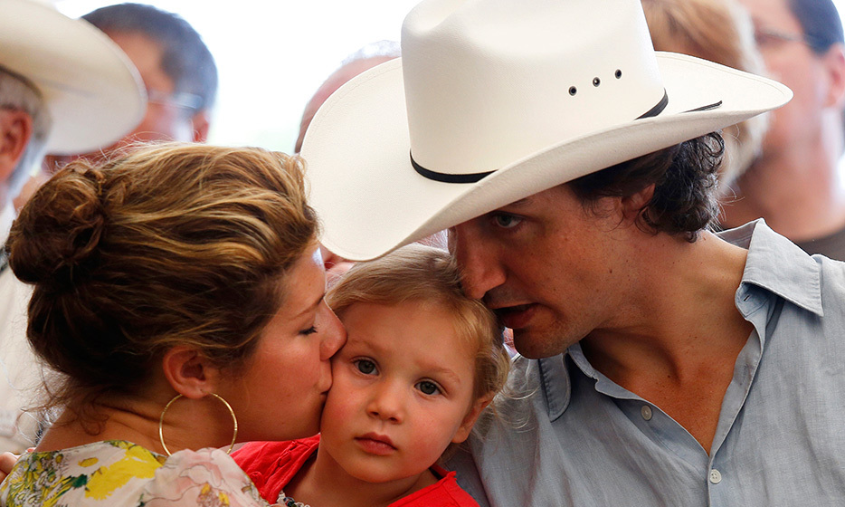 It's an Ella-Grace sandwich! The couple's second child is treated to a double dose of kisses during the Liberal Stampede breakfast marking the 100th anniversary of the Calgary Stampede in the summer of 2012. 
