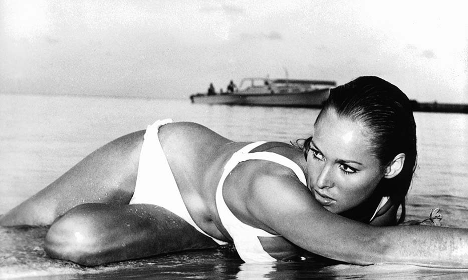 Swiss actress Ursula Andress sprawled on the beach in her now-iconic white bikini, purely the stuff of cinematic history. The original Bond Girl, Ursula appeared in the first James Bond film, 'Dr. No,' in 1962 as Honey Ryder. 