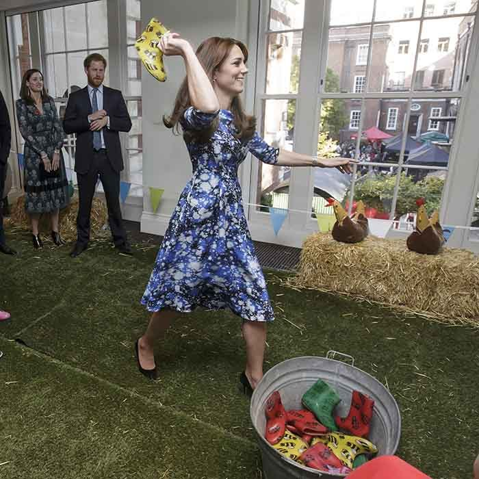 "Kate tried her hand at ""welly wanging,"" or throwing a little wellington (rain boot) to try to knock things over, on Oct. 26 - and she didn't even dirty her gorgeous Tabitha Webb dress! Brother-in-law Prince Harry watches on in the background.