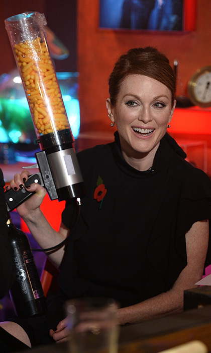 Oscar winner Julianne Moore takes aim with a cheese-puff gun during a live broadcast of <em>TFI Friday</em> at the Cochrane Theatre in London.