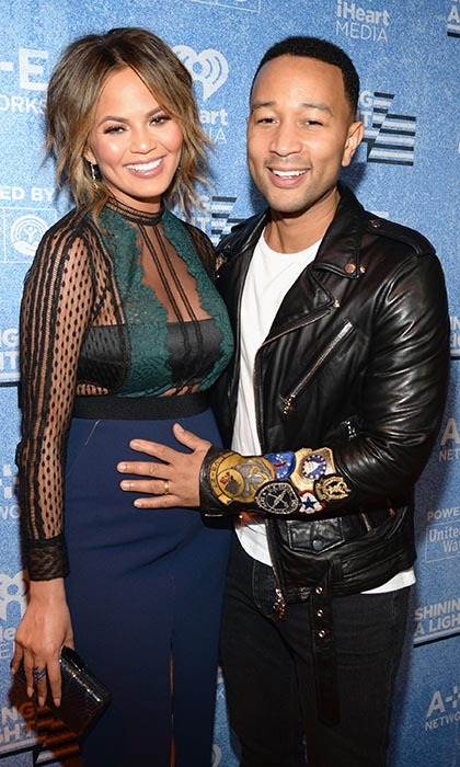 <p>John Legend keeps a protective hold on expectant wife Chrissy Teigen at A+E Network's <em>Shining a Light</em> concert in Los Angeles. </p>