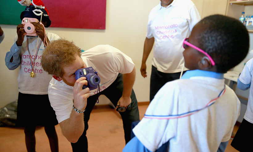 <p>The prince tries his hand at photography, snapping pictures of children at the Mamohato Children's Centre. </p>