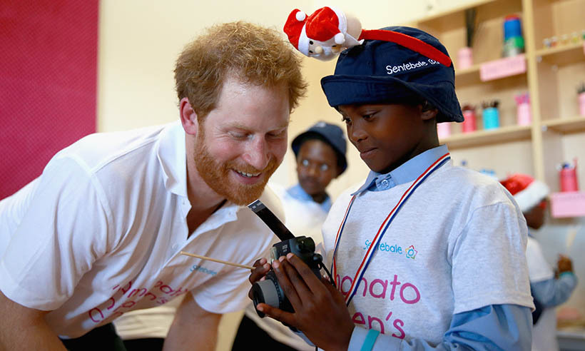 <p> Prince Harry helps a young boy during a photography lesson.</p>