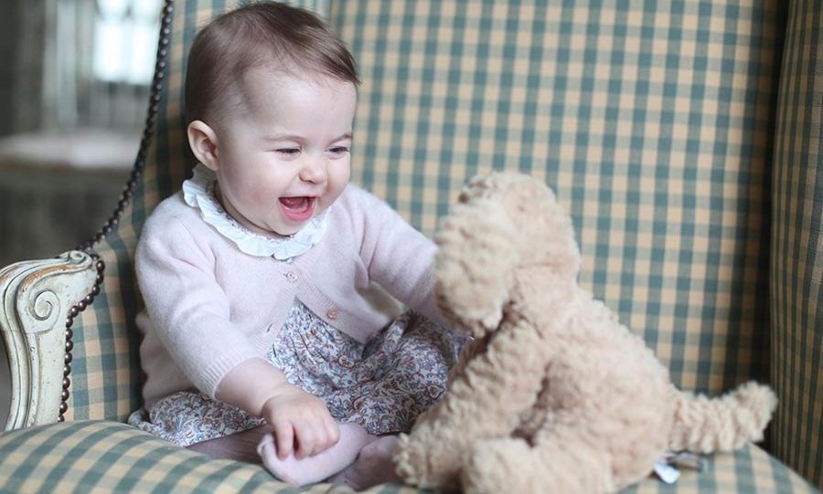 <p> Charlotte giggles as she plays with her stuffed toy.</p>