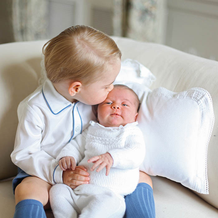 <p>Proud big brother Prince George gave his baby sister, Princess Charlotte, a sweet kiss during the pair's first photo shoot. The darling portrait was photographed by their mom, the Duchess of Cambridge, and released a month after Charlotte's birth on May 2.</p>