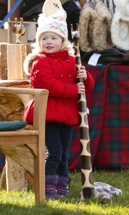 The adorable three-year-old had more fun playing with a wooden giraffe than watching the action at the Duke of Beaufort's Hunt Point-to-Point Race in March 2014. 