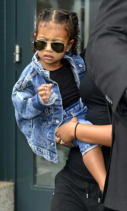 North looks as edgy as her parents in a double denim outfit and oversized sunglasses.
