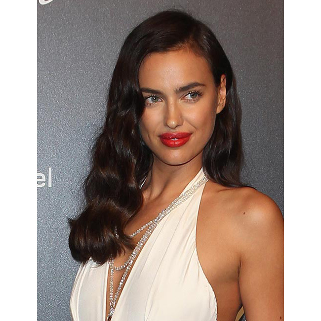 The brunette beauty could have stepped out of old Hollywood with retro loose waves swept to the side, adding an extra touch of glamour by pairing the look with a statement red lipstick.