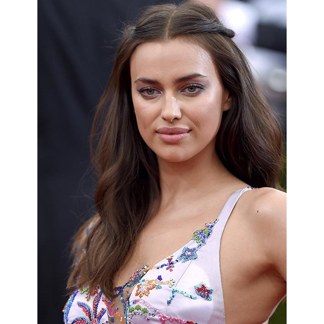 We loved Irina's boho chic hairstyle at the Met Gala – and her effortlessly glamorous look is so easy to recreate. Simply brush your hair through into a middle parting, take the front strands of the left side and create a small plait, pinning it towards the back, and repeat the same on the right side.