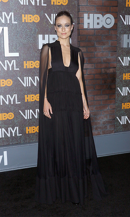 Olivia Wilde was radiant in a black Valentino cape gown at the premiere of her new HBO series, <i>Vinyl</i>. She topped it off with a veiled headpiece for a retro vibe.