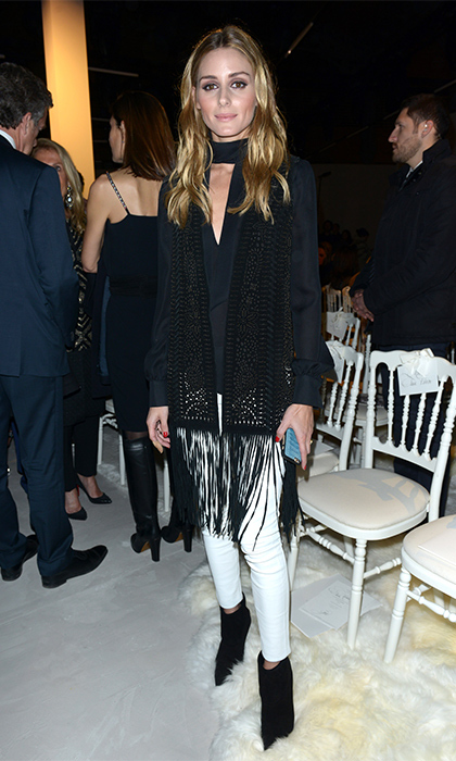 Olivia Palermo has been wearing hit after hit at Paris Haute Couture Fashion Week, and thought this ensemble may appear simple at first, the power of its French-woman coolness is in the details. A perfectly fitted black blouse and white leather pencil pants are anchored by black booties and topped off with a covet-worthy fringed suede scarf. 