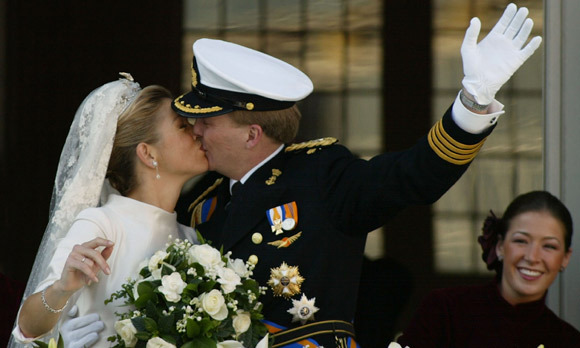 The kiss seemed to be eternal as Willem-Alexander and his wife, the newly-styled Princess Máxima, stepped onto the balcony of the royal palace - which was garlanded with white blooms for the occasion - to wave to their people.