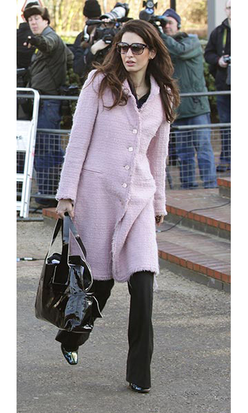 Arriving for a court case in London, keeping warm in a pale-pink coat.
