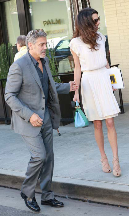 Amal stepped out for lunch in Beverly Hills with husband George Clooney wearing a white pleated dress and nude strappy sandals. She teamed the ensemble with a turquoise and green clutch bag.
