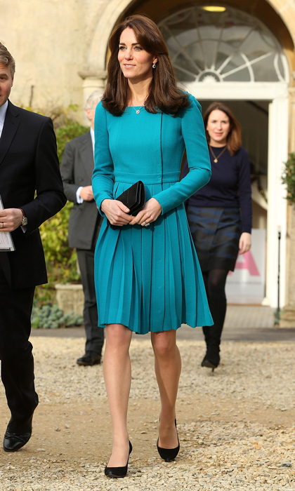 Emilia Wickstead's pleated dress coat with a high neckline is such a classic look for Kate that she has it in two colours! In addition to sporting this vibrant turquoise version, the mother of two also has it in baby pink. 