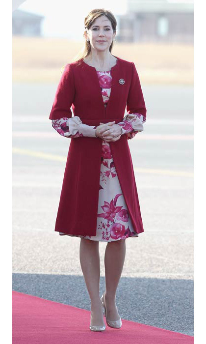 Pairing pretty florals with a fit-and-flare coat as she greeted the Prince of Wales and Duchess of Cornwall at Copenhagen airport. 