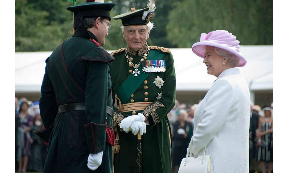 Stewart Parvin, pink silk dress with coordinating white jacquard coat and pink hat designed by milliner Philip Somerville worn by Her Majesty The Queen for a garden party in 2009.