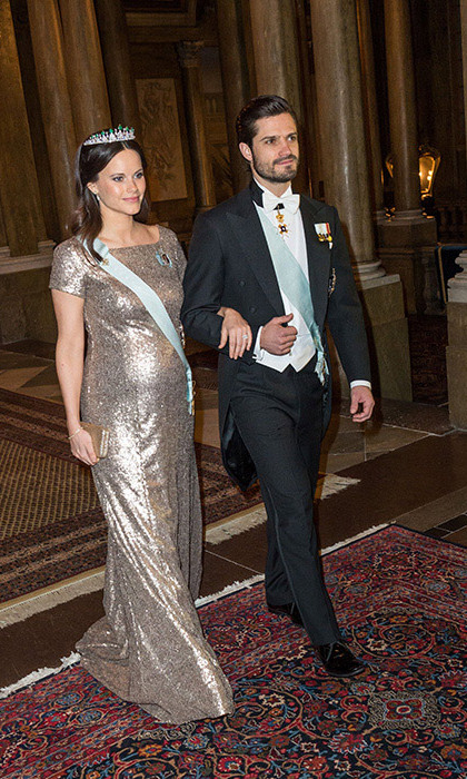 Walking arm in arm with her husband, Prince Carl Philip, Sofia dazzled in a floor-length gold sequinned gown and brooch, teamed with a sash and a diamond and emerald-encrusted tiara for an official dinner at the palace. <p>Photo: © Rex</p>