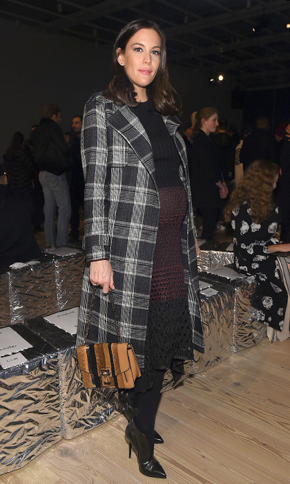 Liv Tyler (and her adorable baby bump!) attended the Proenza Schouler Fall 2016 runway show at New York Fashion Week in a knit dress and Proenza Schouler plaid coat. 