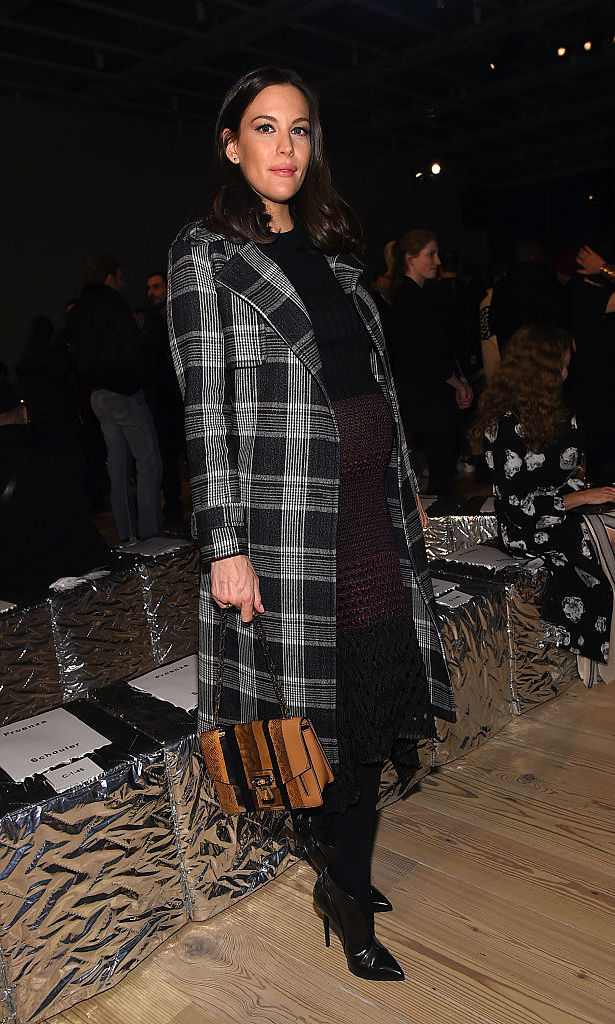 A stylish Liv Tyler showed off her growing baby bump at the Proenza Schouler fashion show.