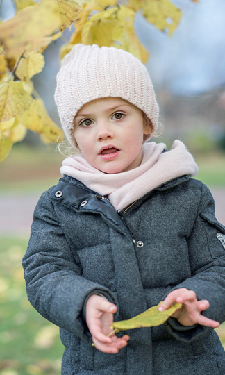 November 2015: The fashionable youngster bundled up against the autumn chill in a padded grey coat with a knitted pink hat and matching scarf.
