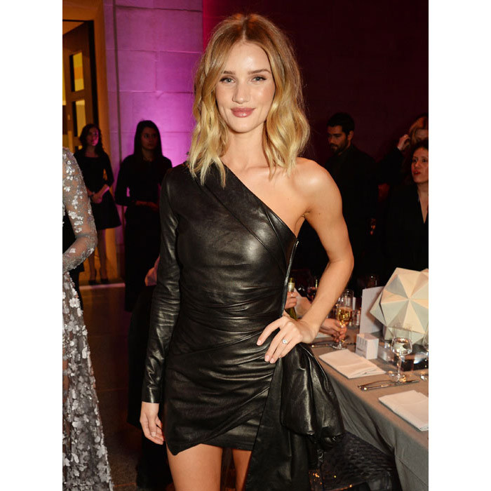 Newly engaged Rosie Huntington-Whiteley looked stunning in a leather minidress that showed off her supermodel physique.