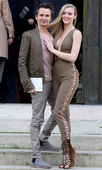 Matthew Bellamy and Elle Evans arrived and stayed close during the Balmain fashion show.