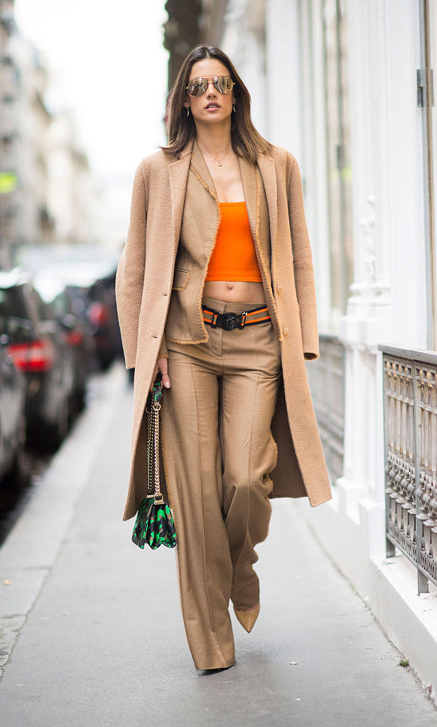 Supermodel Alessandra Ambrosio made the streets of Paris her personal runway wearing a coat from Ports, paired with Versace pants and top and Christian Louboutin shoes.