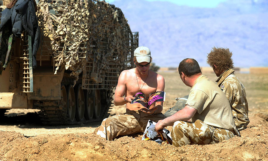 <p>A shirtless Prince Harry read a magazine near his Spartan armored vehicle in the desert on February 19, 2008 in Helmand Province, Afghanistan.