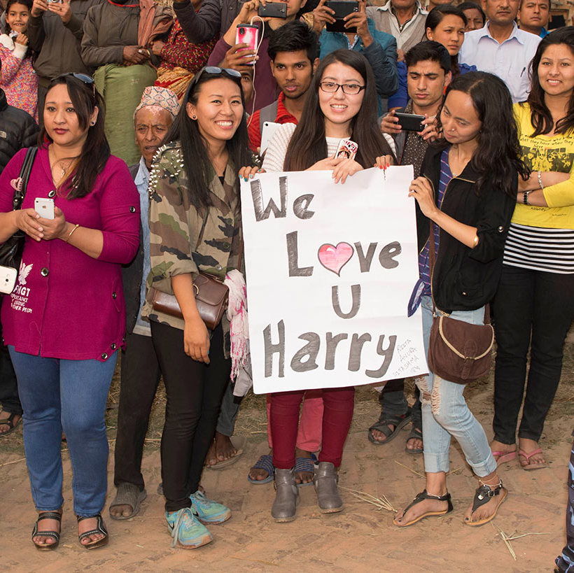 "The royal was greeted by a group of girls holding up a sign that read ""We love u Harry"".