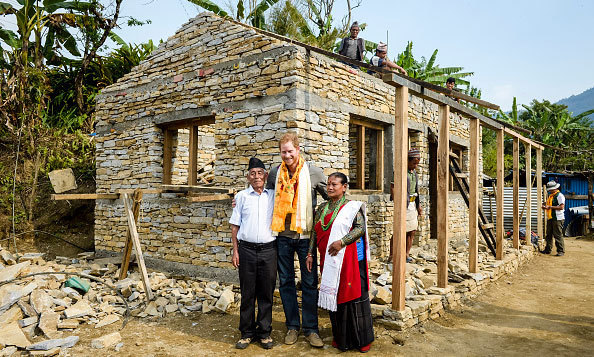 Prince Harry posed with a couple and their newly-built earthquake-proof house in Bhir Kuna while visiting the earthquake stricken village.
