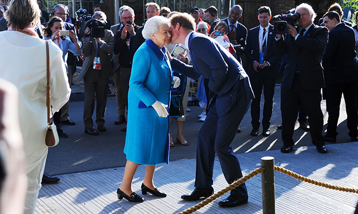 """I've been asking her what her secret is for years,"" quips grandson Harry, seen here giving Her Majesty a kiss.