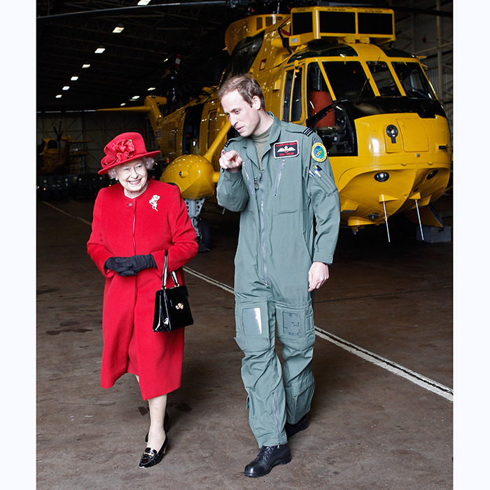 The Queen is escorted by her grandson William during a visit to RAF Valley, where the prince was stationed as a search and rescue helicopter pilot in 2011.