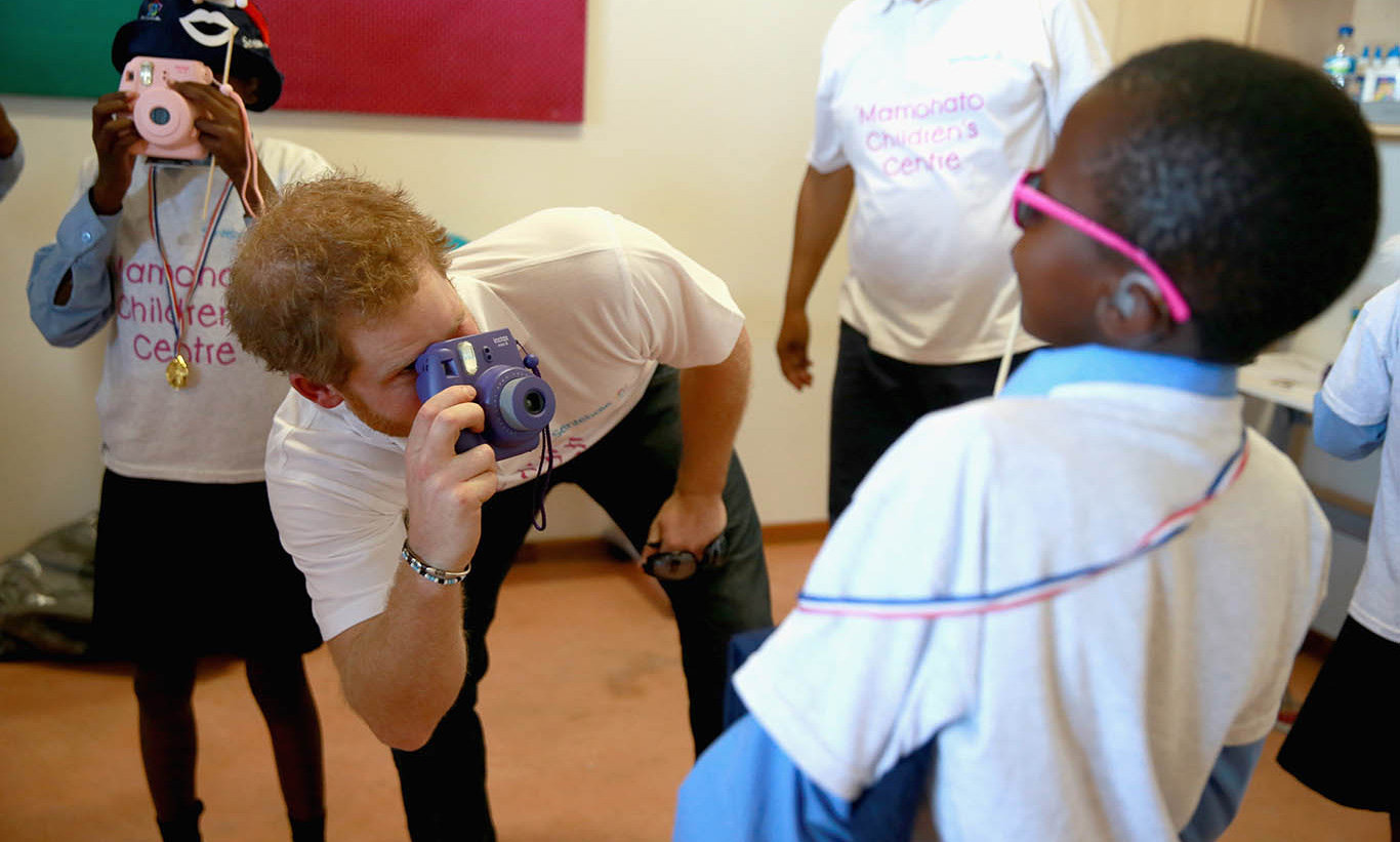 November 2015: Prince Harry had some fun with the kids during a photography activity at the Mamohato Children's Centre in Lesotho, where colourful Fuji Instax cameras were the order of the day.