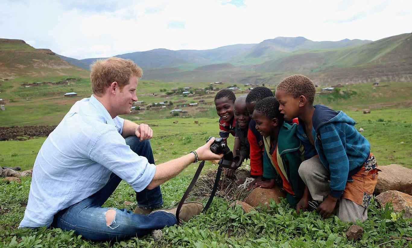 December 2014: Prince Harry showed the kids of Lesotho some of the pictures from his visit.