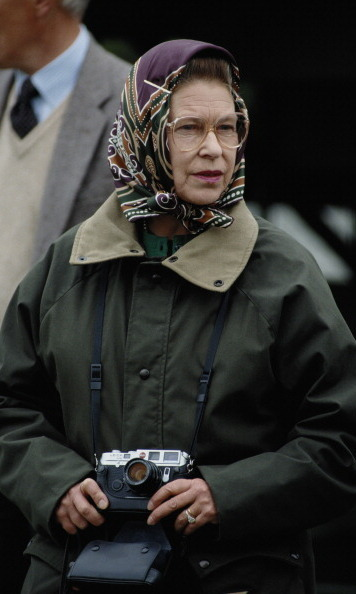 May 1989: Queen Elizabeth accessorized with a camera and headscarf during the Royal Windsor Horse Show.