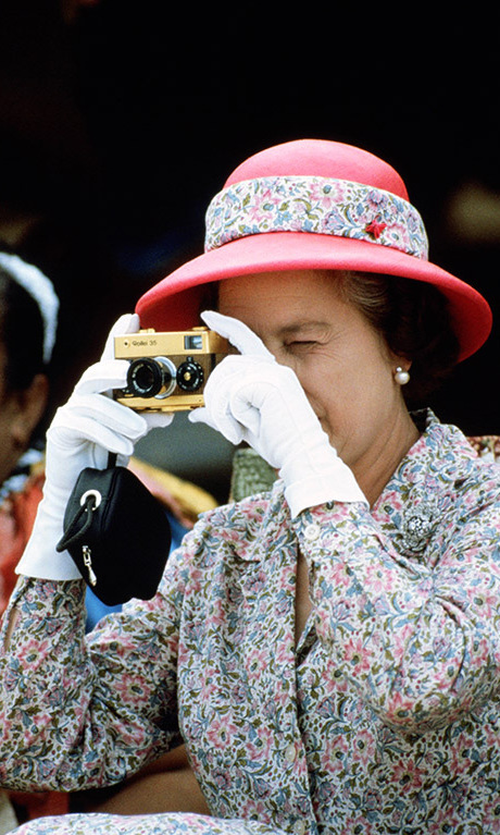 October 1982: Queen Elizabeth took in the sights and grabbed her classic camera for a quick snap during a visit to Tuvalu.