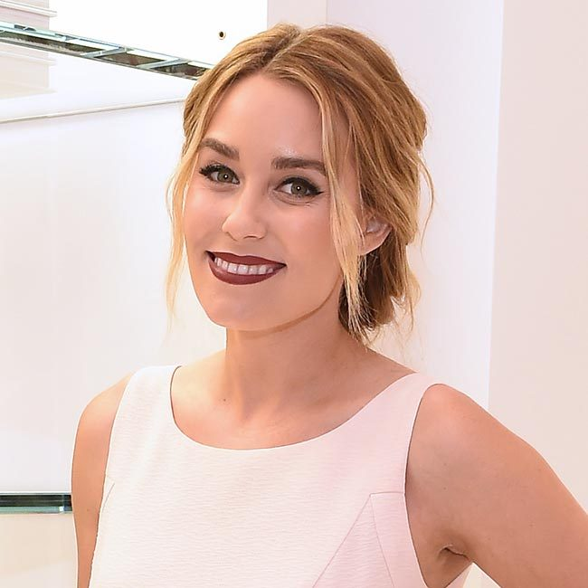 <p>Lauren wowed at the book's official launch when she swept her blonde tresses back into an elegant bun, leaving strands loose at the front to frame her face – and we love the way she teamed it with on trend statement berry lipstick and winged eyeliner for ultimate laidback glamour.