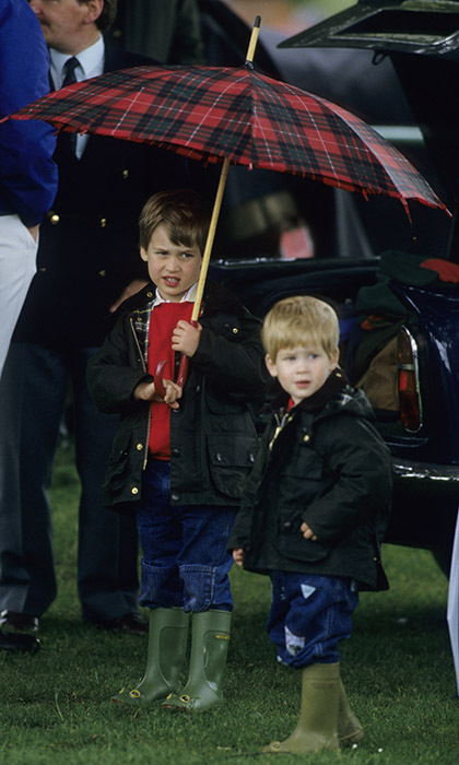 Like a good big brother, Prince William, then five, kept two-year-old Prince Harry dry during an outing in Gloucestershire in 1987. 