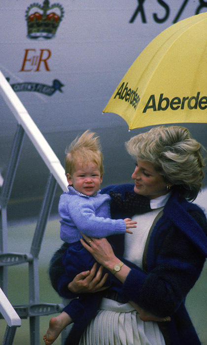 Princess Diana does her best to shield one-year-old Prince Harry from the rain in Aberdeen in 1985. 