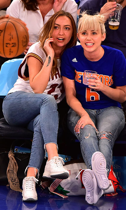 Miley Cyrus, sporting her sparkly engagement ring from Liam Hemsworth, kicked back at the New York Knicks game with her big sister Brandi.