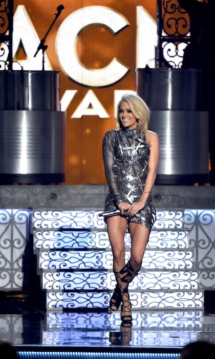 "Carrie then took the stage to perform her new single, ""Church Bells,"" in a metallic-silver Manual Diaz minidress. Carrie showed off her toned legs in this one-sleeved cage dress and custom strappy heels. Graziela Gems earrings and Mariana Harutunian bracelet and rings added even more shine to her outfit.