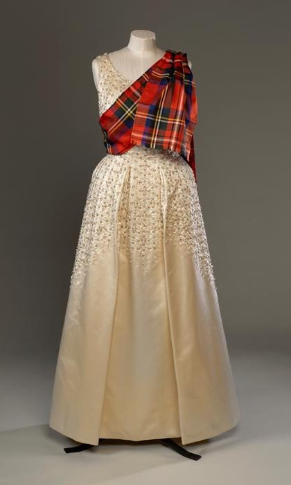 Norman Hartnell, who first worked for the then Princess Elizabeth in the 1940s, also created the evening dress of embroidered duchesse satin worn by The Queen with a sash of Royal Stewart tartan for the Gillies Ball at Balmoral Castle in 1971.