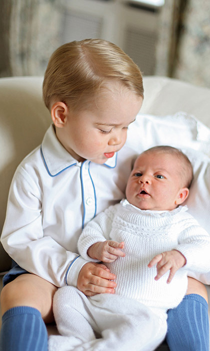 Prince George keeps a protective eye over his baby sister Princess Charlotte during the young royal's first official portrait photo shoot. 