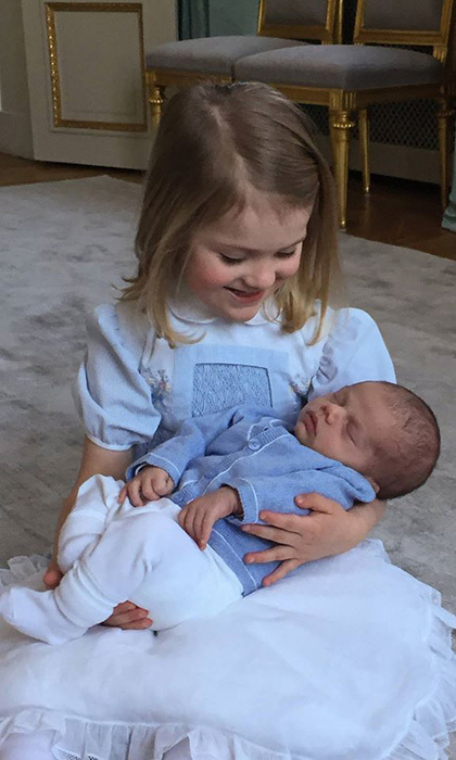 Sweden's Princess Estelle cradles her baby brother Prince Oscar. 
