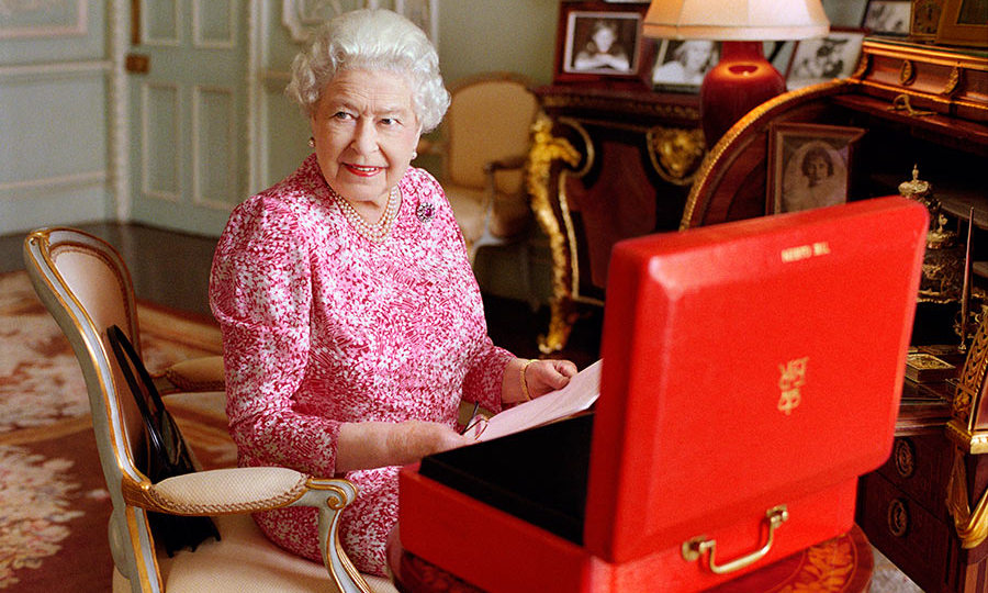 In this handout photo released by Buckingham Palace on September 8, 2015, Queen Elizabeth II is seated at her desk in her private audience room at Buckingham Palace with one of her official red boxes which she has received almost every day of her reign and contain important papers from government ministers in the United Kingdom and her Realms and from her representatives across the Commonwealth and beyond. The photo has been taken by Mary McCartney in July 2015, to mark the moment she becomes the longest reigning British Monarch.