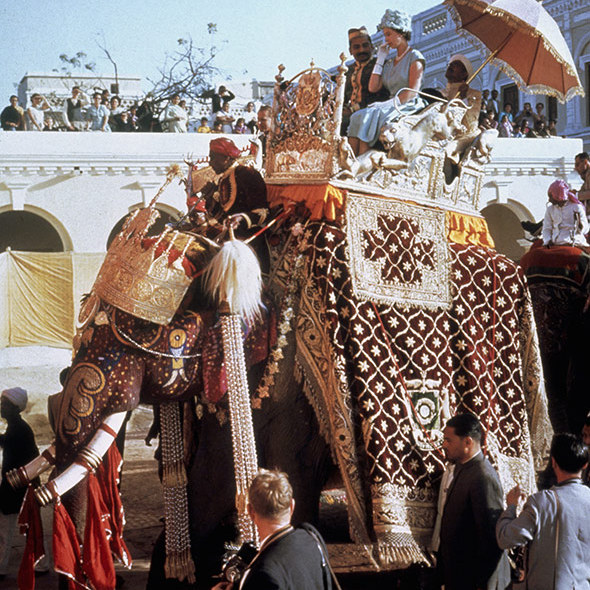 Queen Elizabeth II perches in a howdah on the back of an elephant at Benares, during her tour of India, 25th January 1961.